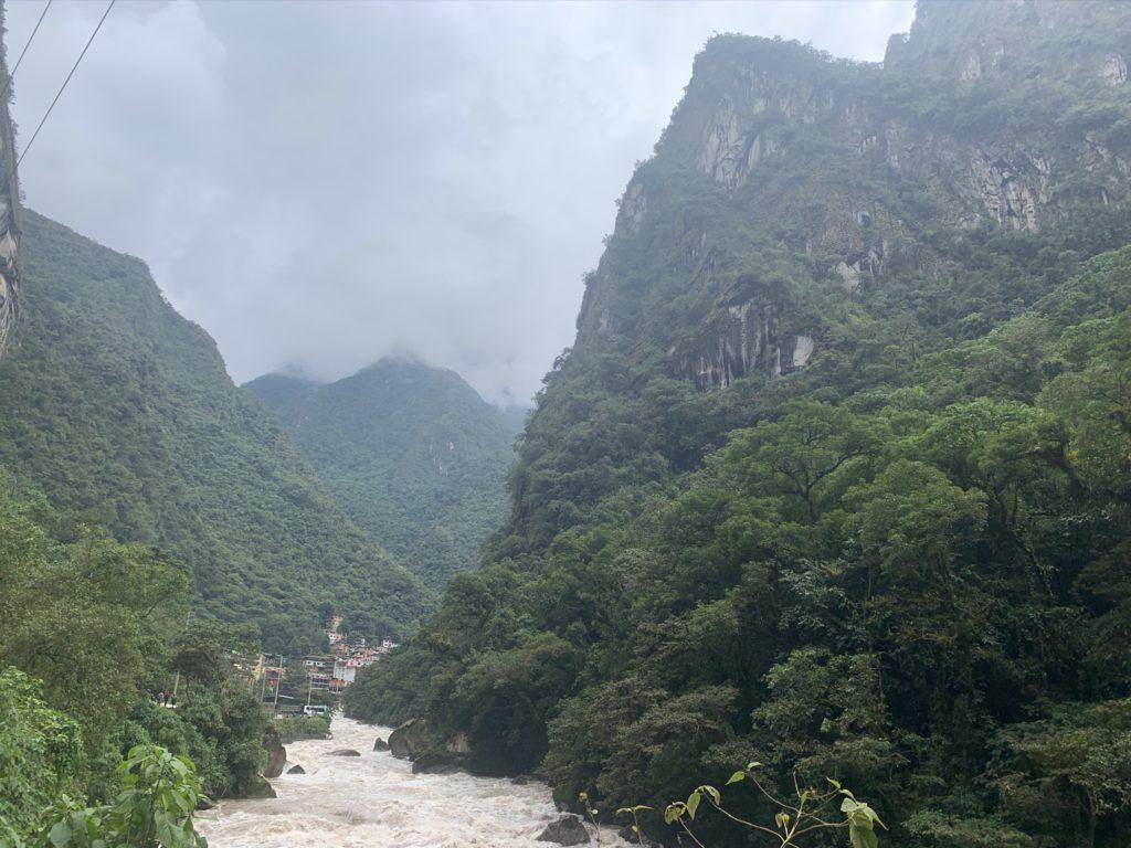 Die Stadt Aguas Calientes liegt zwischen bewaldeten Bergen am Fluss Urubamba