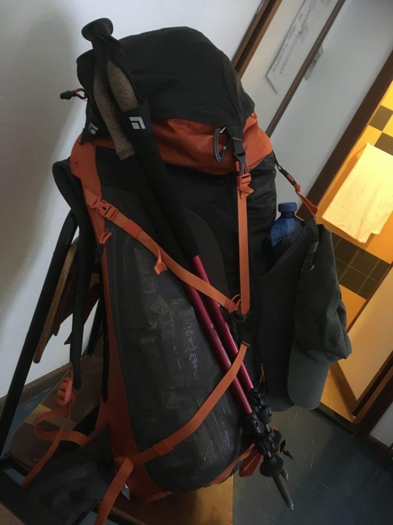 Ein vollgepackter Rucksack mit Wanderstöcken