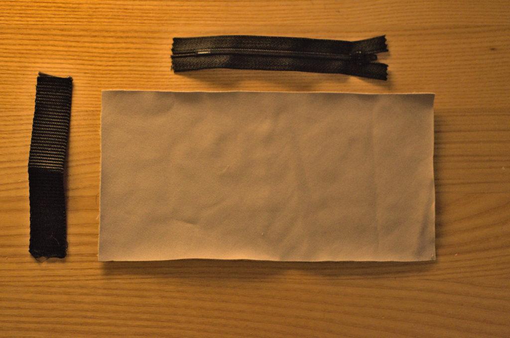 Die benötigten Materialien für die Tasche: Ein Stück Stoff, ein Reißverschluss und ein Gurtband.