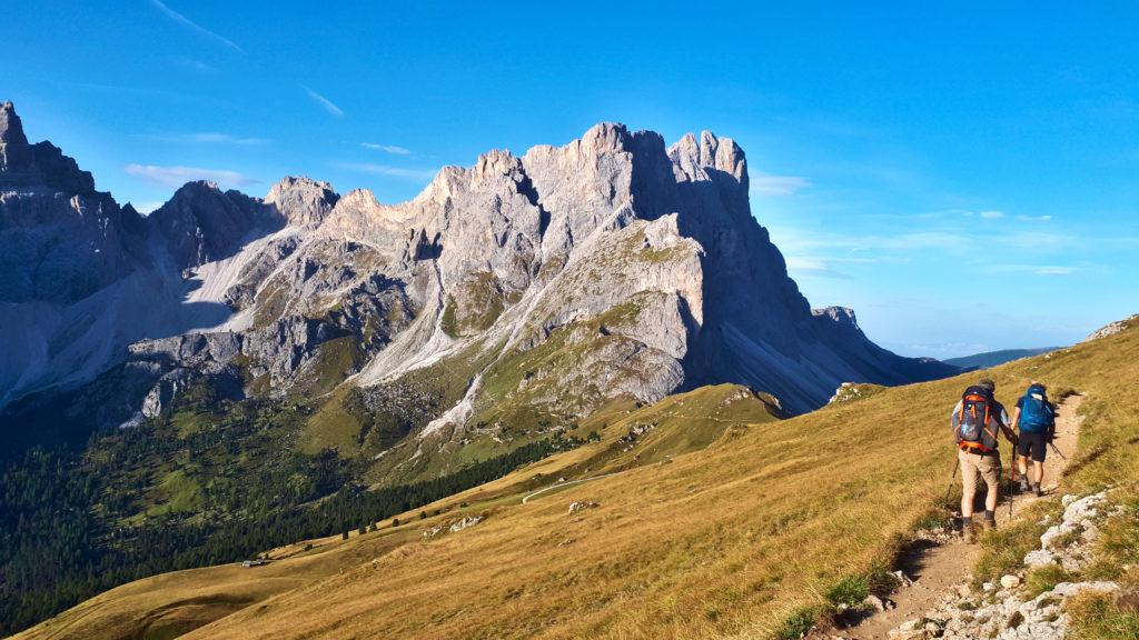 Dolomitengipfel in der Sonne, mit zwei Wanderern im Vordergrund. Das Bild stellt einen Ausblick auf die Alpenquerung bereit.