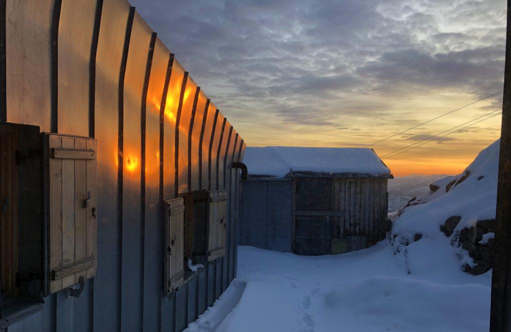 Eine Berghütte im Sonnenuntergang.