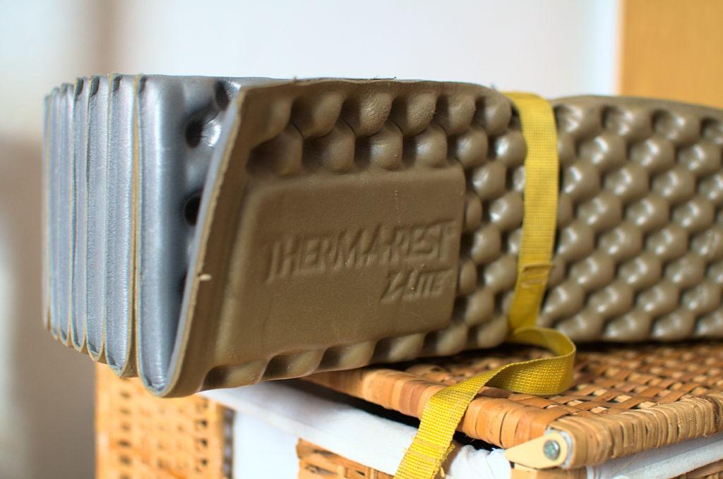 Eine zusammengefaltete ThermaRest Z-Lite Isomatte, die von einem gelben Gurtband zusammengehalten wird.