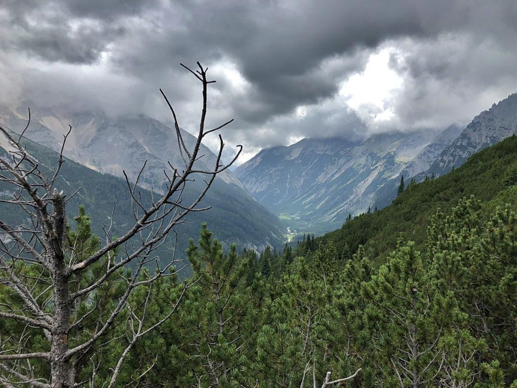 Ein Gebirgstal über dem sich Gewitterwolken zusammenziehen.